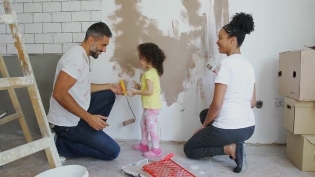 Beautiful home for beautiful family Young family pregnant mother , father and daughter painting walls in flat renovation stock videos & royalty-free footage