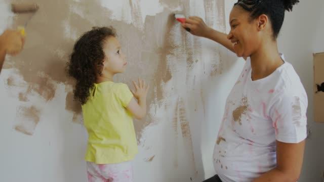 vackra hem för vackra familj - painting wall bildbanksvideor och videomaterial från bakom kulisserna