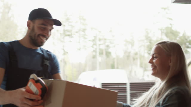 Beautiful Homeowner Opens the Door to Smiling Delivery Man and Receives Parcel After Signing on Electronic Signature Device. video