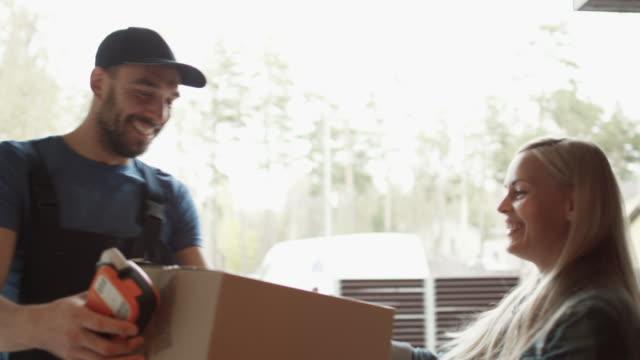 美麗的房主打開門, 微笑的交付人和接收包裹簽署後, 電子簽名設備。 - postal worker 個影片檔及 b 捲影像