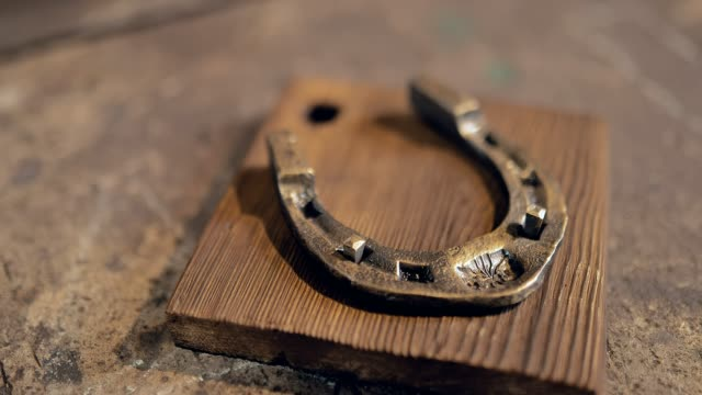beautiful horseshoe. plated with gold. souvenir. close-up - horseshoe stock videos & royalty-free footage