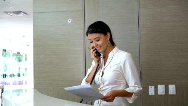 beautiful hostess at the reception answering the call from a guest - hotel checkin video stock e b–roll