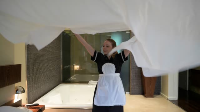 beautiful house keeper making the bed at the hotel putting the bed sheet on the bed smiling - обслуживание стоковые видео и кадры b-roll