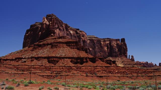 schöne große rote felsformationen in der wüste. kontrastierende gegen die klaren blauen sommerhimmel und die leuchtend grüne sträuchern. ursprünglich auf rote drachen in sechs kilometer. - kontrastreich stock-videos und b-roll-filmmaterial