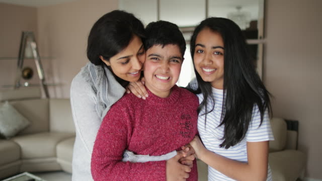 A Beautiful Indian Family A mother is standing in her living room with her son and daughter as they hug and smile for the camera. autism stock videos & royalty-free footage
