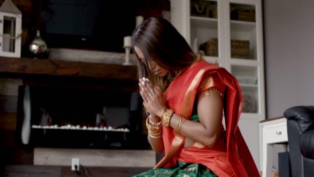 beautiful indian female praying inside her home - sari filmów i materiałów b-roll