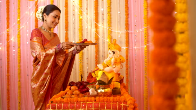 beautiful indian woman worshipping lord ganesha with pooja ki thali - festival celebration - hinduizm filmów i materiałów b-roll