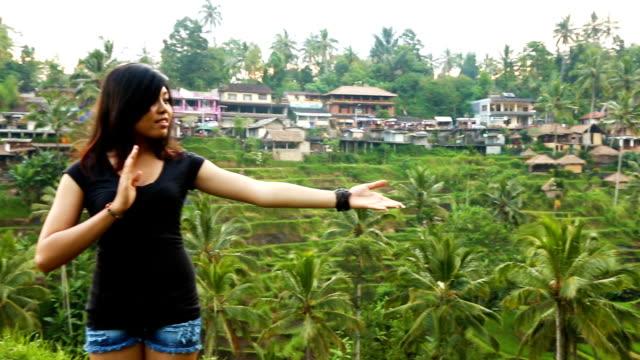 インドネシアの美しい若い女性に挨拶して段畑 hd を示しています - 自然旅行点の映像素材/bロール