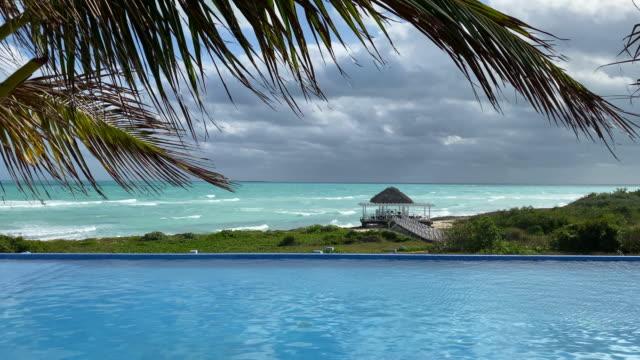 vídeos de stock, filmes e b-roll de linda piscina infinita e gazebo na praia de areia branca tropical - estação turística