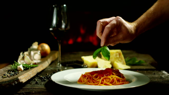 beautiful italian pasta composition in old traditional cottage with fireplace and relax atmosphere with chef garnish plate with parmesan cheese and basil leafs beautiful italian pasta composition in old traditional cottage with fireplace and relax atmosphere with chef garnish plate with parmesan cheese and basil leafs pesto sauce stock videos & royalty-free footage