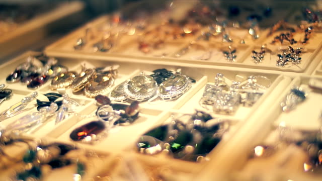 vídeos de stock e filmes b-roll de beautiful jewelry on store shelves sparkle in the rays of light - jóias