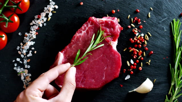 Beautiful juicy fresh meat steak on a table with salt, rosemary, garlic, and tomato on a black background, top view
