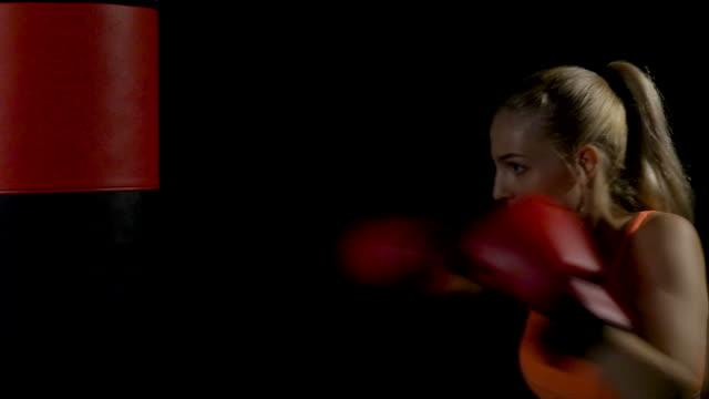 vídeos de stock, filmes e b-roll de bela kickboxing mulher treino saco de pancadas na escuridão. - autodefesa