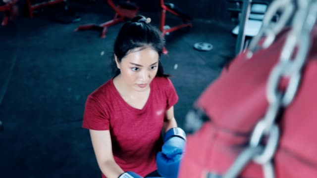 vídeos de stock e filmes b-roll de beautiful kickboxing woman training with the punching bag in a gym, slow motion - boxe tailandês