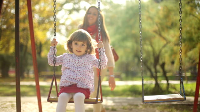 beautiful kid and mother play outdor on swing beautiful kid and mother play outdor on swin swinging stock videos & royalty-free footage