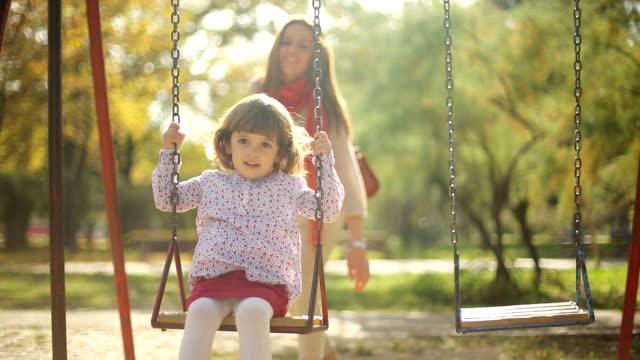 schönes kind und mutter spielen outdor auf schaukel - kinderspielplatz stock-videos und b-roll-filmmaterial