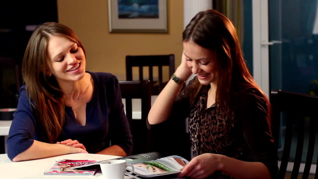 Beautiful ladies chatting in cafe smiling reading magazine laugh video