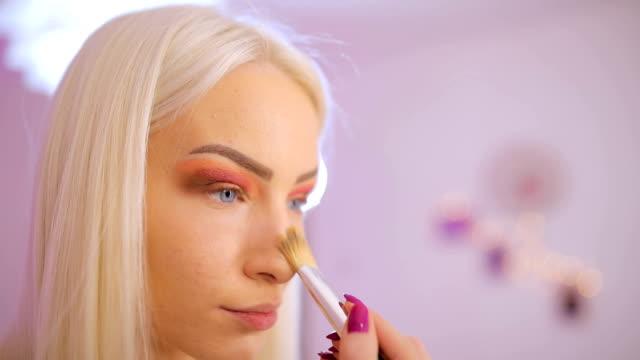Beautiful lady applying make up on face