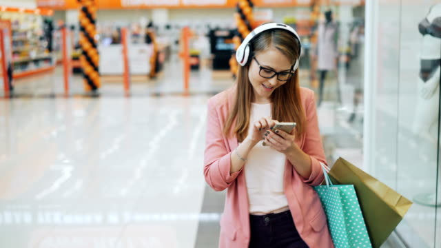Beautiful lady in headphones is listening to music and using smartphone walking in shopping mall with paper bags. Modern gadgets, millennials and happiness concept.