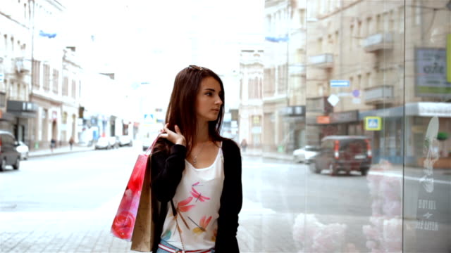 beautiful lady keeps packages on shoulder and looking at the boutiques video