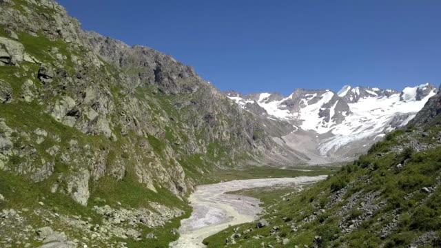piękne góry krajobrazowe szczyty śniegu. rzeka w górskiej dolinie - mountain top filmów i materiałów b-roll