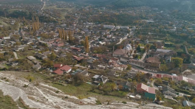 Beautiful landscape of a town located between the hills in the lowlands. Shot. View from the top of the hill