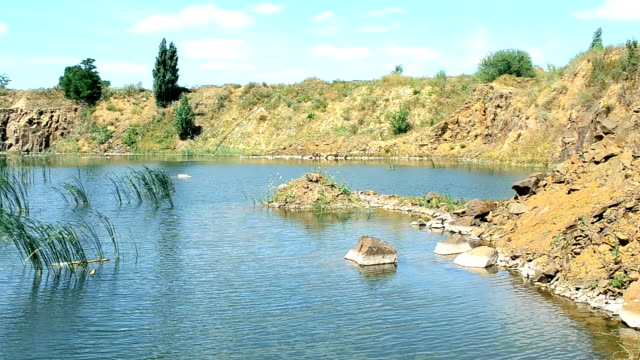 Beautiful landscape of lake in summer with basalt rocks, stones, calm water video