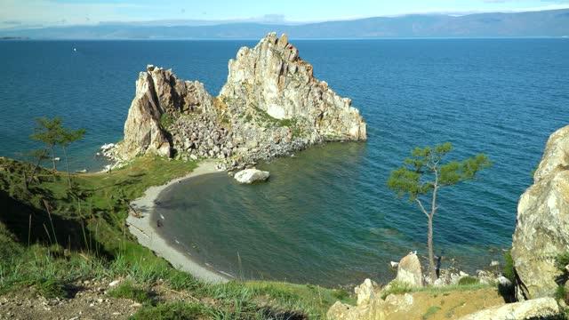 vídeos de stock e filmes b-roll de beautiful landscape of siberian baikal lake. panoramic view of shamanka rock on olkhon. cape burhan. concept of travel. lake baikal is the longest freshwater lake in the world. natural background. - lago baikal