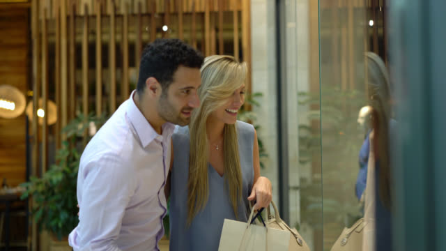 vídeos de stock e filmes b-roll de beautiful latin american couple at the mall looking at the store window pointing while talking - centro comercial