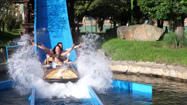 beautiful latin american family on a log ride at an amusement park having fun with arms up - roller coaster stock videos & royalty-free footage