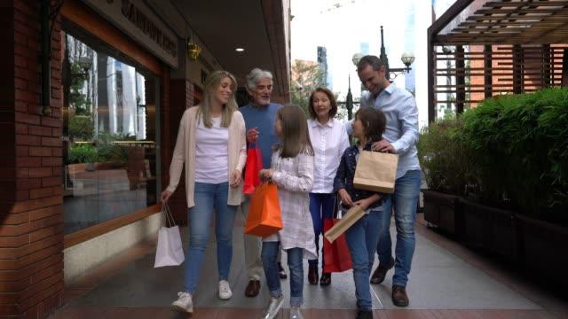 vacker latinamerikansk familj med mor-och far föräldrar på köp centret shopping och ha roligt - spendera pengar bildbanksvideor och videomaterial från bakom kulisserna