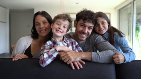 vidéos et rushes de belle famille américaine latine avec deux enfants souriant à l'appareil-photo très heureux tout en s'asseyant sur le divan - personnes belles