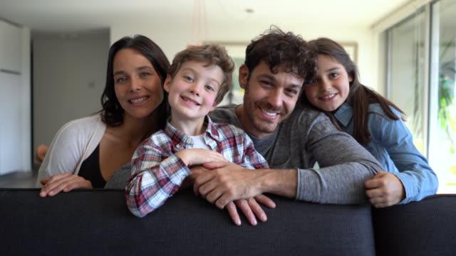 소파에 앉아있는 동안 카메라에 매우 행복 미소 두 아이와 아름다운 라틴 아메리카 가족 - 이를 드러낸 미소 스톡 비디오 및 b-롤 화면