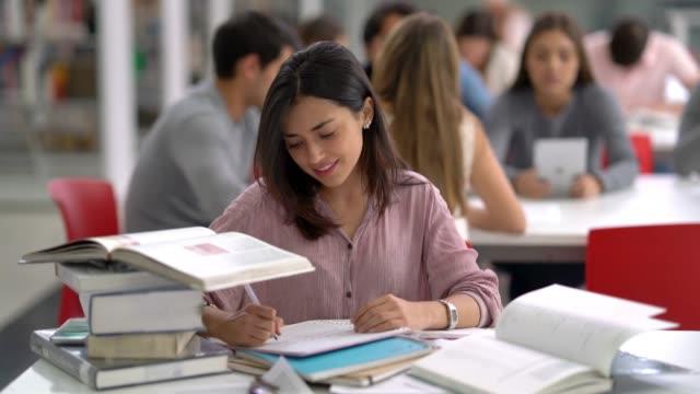 schöne lateinamerikanische studenten sitzen in der bibliothek studium für eine prüfung, ein buch und notizen zu betrachten - akademisches lernen stock-videos und b-roll-filmmaterial