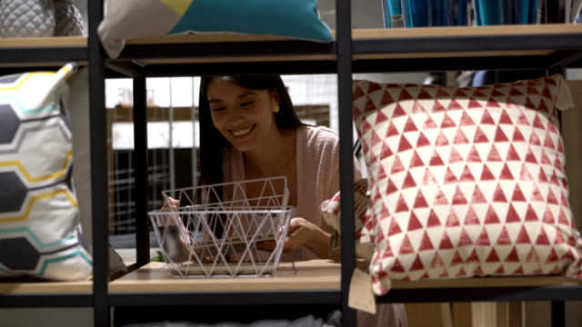 beautiful latin american woman at a store looking at a basket on shelf very happy - arredamento video stock e b–roll