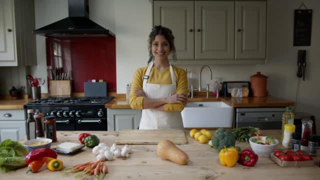 vídeos y material grabado en eventos de stock de hermosa mujer latinoamericana en casa con verduras frescas deliciosas en el mostrador listo para preparar una comida vegana sonriendo a la cámara - woman cooking