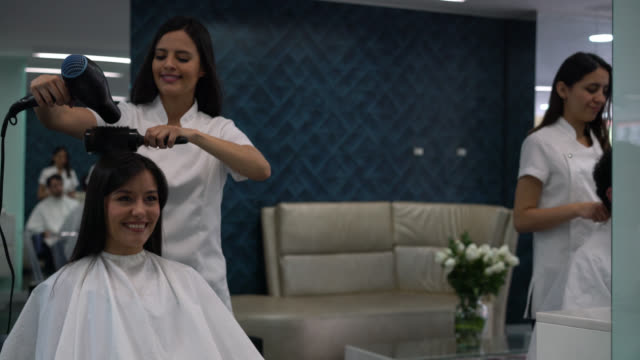 Beautiful latin american woman at the hair salon getting a hairdo looking very happy at the mirror Beautiful latin american woman at the hair salon getting a hairdo looking very happy at the mirror and smiling hairstyle stock videos & royalty-free footage