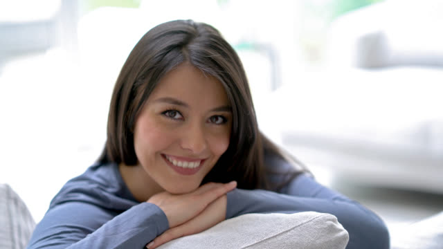 Beautiful latin american woman sitting on the couch and smiling video