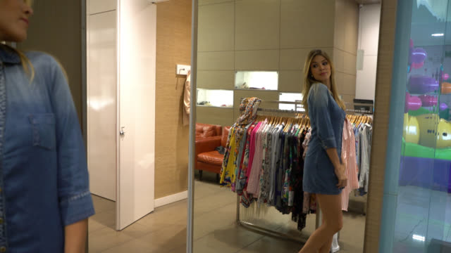 beautiful latin american woman trying on a dress in the fitting room and looking at the mirror very happy - modella negozio video stock e b–roll