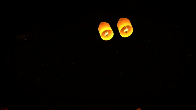beautiful lead couple Lanterns flying in night sky video