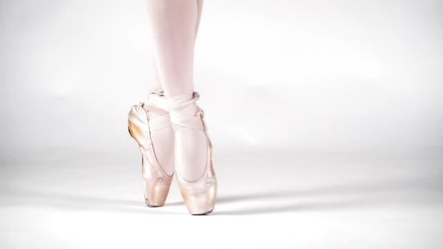 schöne beine einer ballerina in pointe auf weißem hintergrund, nahaufnahme. klassisches tanzballett. zeitlupe. - ballettröckchen stock-videos und b-roll-filmmaterial