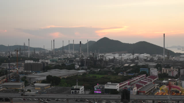 Beautiful lighting of oil refinery plant petrochemical industry and transport and Highway traffic and Oil refinery at Sunset time, Business logistics concept and Oil refinery at Sunset time, Zoom out