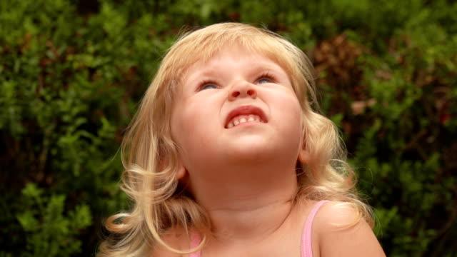 vacker liten blond flicka ler och tittar på himlen - förskoleelev bildbanksvideor och videomaterial från bakom kulisserna