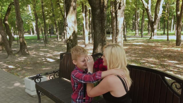 Beautiful little boy gives a bouquet of flowers to his beloved mother in the park on a bench