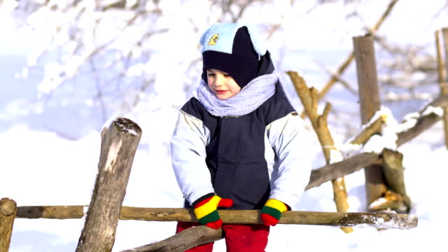 vídeos de stock e filmes b-roll de beautiful little boy in winter park. he sits on a wooden fence and plays with a stick. - roupa quente
