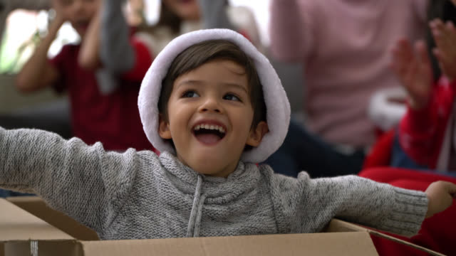 Beautiful little boy popping out from a box during christmas celebration at home video