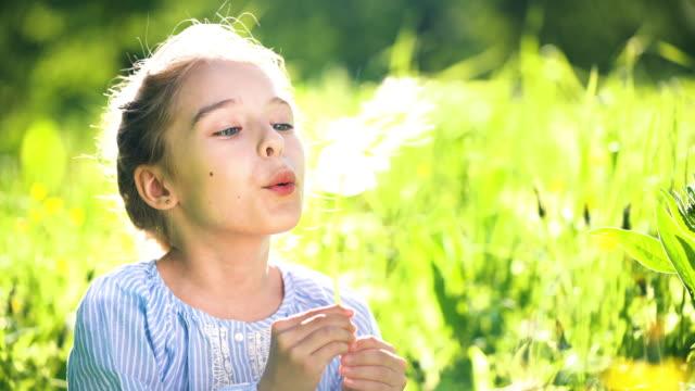 vacker liten flicka på solig sommar dag blåser mask ros på grön äng. sommar roligt koncept. - endast flickor bildbanksvideor och videomaterial från bakom kulisserna