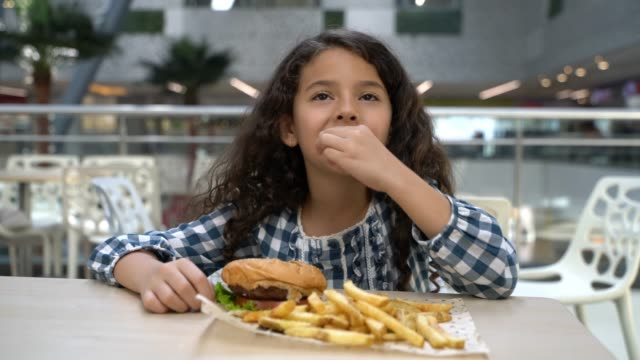 Beautiful little girl at the food court mall enjoying a hamburger and fries
