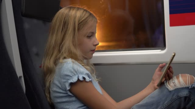 Beautiful little girl commuting on train texting on her smartphone