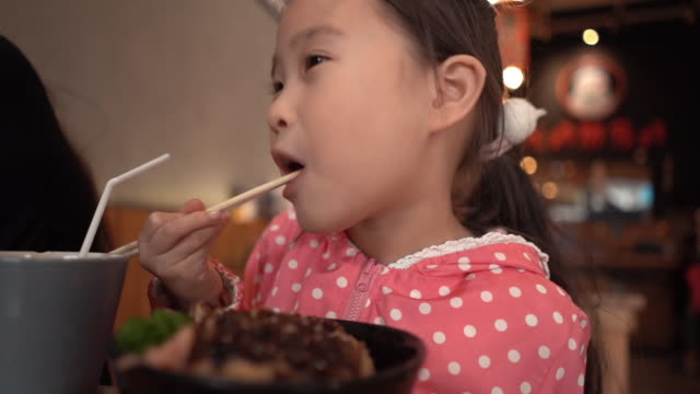 vídeos de stock e filmes b-roll de beautiful little girl eating fried pork rice tonkatsuin in japanese restaurant - tempura